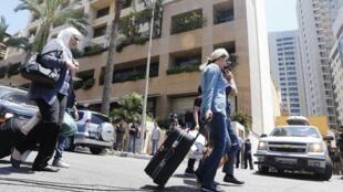 Des clients quittent les lieux lors du raid contre l'Hôtel Duroy, à l'ouest de Beyrouth, le 26 juin 2014.