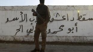 Un combattant de l'Armée syrienne libre (ASL) devant un graffiti appelant à la fin de l'influence de l'EIIL en Syrie. Banlieue d'Alep, 7 janvier 2014.