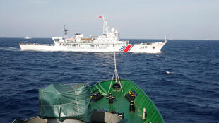 Một tầu hải cảnh Trung Quốc (trắng) gần một con tầu của cảnh sát biển Việt Nam tại Biển Đông, khoảng 210 km (130 hải lý) ngoài khơi Việt Nam, ngày 14/05/2014.