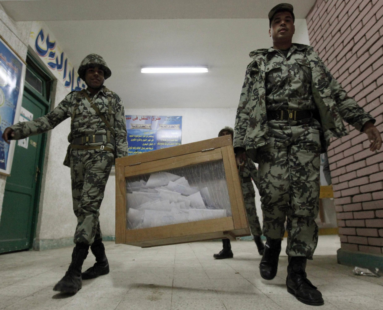 Soldados do Exército egípcio carregam caixa lacrada com votos nesta quarta, último dia de eleições legislativas no país.