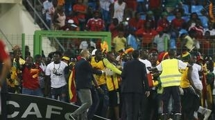 Officials try to protect Ghana fans after Equatorial Guinea fans threw objects during the African Nations Cup semi-final soccer match in Malabo, 5 February 2015.