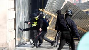 Un groupe de black blocs cassant une vitrine lors d'une manifestation à Paris.