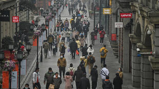 People walk along a street in Wuhan on Saturday, one year after the city went into lockdown to curb the spread of Covid-19