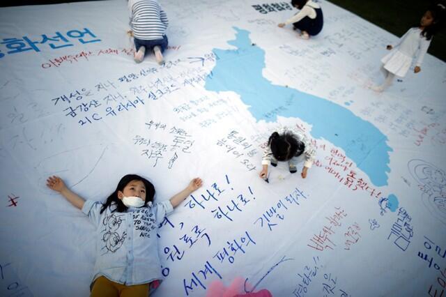 Crianças brincam em uma bandeira unificada com mensagens que desejam uma cúpula bem sucedida entre coreanos no centro de Seul, na Coreia do Sul, em 21/04/2018