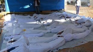 Ativistas sirios inspeccionan cuerpos de víctimas del presunto ataque químico del 21 de agosto de 2013, en la región de Damasco.