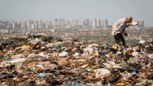 La extrema pobreza castiga al Brasil, una persona escarbando en uno de los mayores basurales de América latina, Lixao da Estrutural,  Brasil