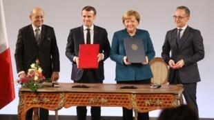 Entre os ministros das Relações Exterioriores Jean-Yves Le Drian (esq.) e Heiko Maas (dir.), Macron e Merkel assinam a modificação do Tratado do Eliseu em Aachen, no extremo oeste da Alemanha.