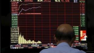 Investidor consulta informações da bolsa de Xangai.
