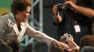 Dilma Roussef saluda  a la multitud en Brasilia tras su victoria electoral.