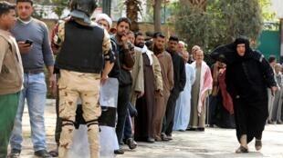 Les gens font la queue pour voter, lors du référendum constitutionnel, dans un bureau de vote au Caire, le 20 avril 2019.