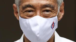 Le secrétaire général du Parti d'action du peuple et le Premier ministre singapourien Lee Hsien Loong avec un masque orné du logo de son parti, le 30 juin 2020.