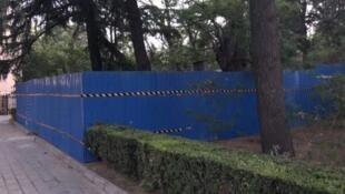 圖為清華大學校園被藍色圍欄圍住的題有民主、自由碑文的王國維紀念碑