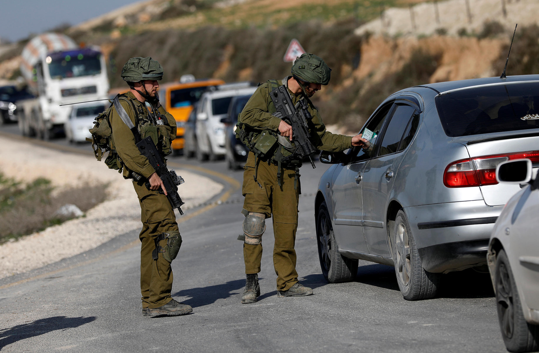 Des soldats israéliens contrôlent l'identité d'un chauffeur à un checkpoint près de Naplouse, en Cisjordanie, le 10 janvier 2018.