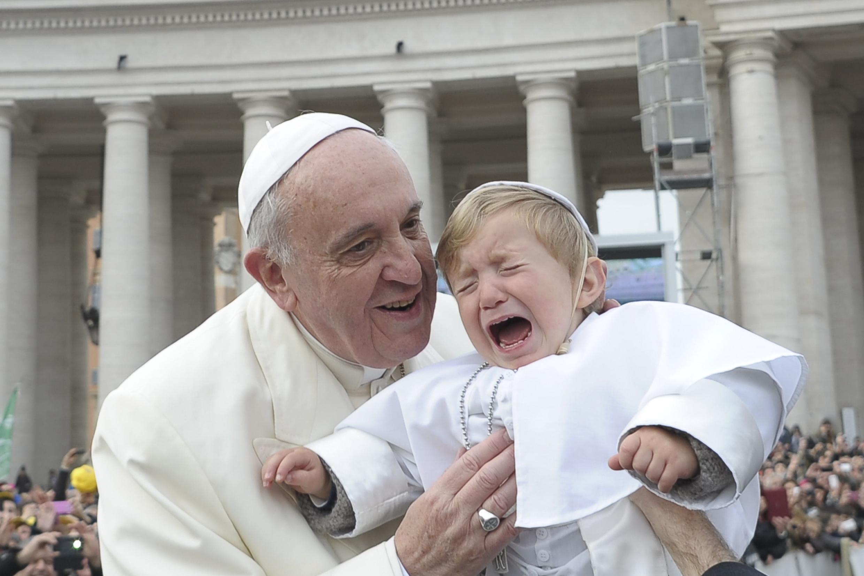 Đức Giáo hoàng Phanxicô bế một trẻ nhỏ trước khi Ngài làm lễ ở quảng trường Saint Pierre, Vatican, 26/02/2014