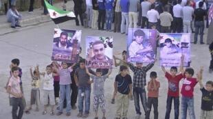 Crianças carregam imagens de familiares mortos pelo regime em Deraa.