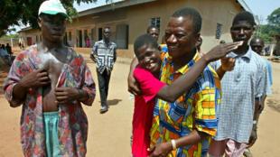 Grégoire Ahongbondon (C), responsable de l'association Sainte-Camille, est entouré de malades mentaux dans un centre médical de Bouaké, en 2003. Son association humanitaire a lancé un appel à l'aide pour poursuivre ses activités.