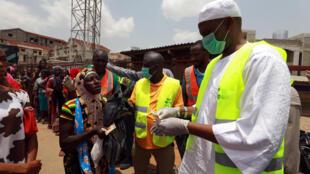 疫情下等待发放食物补助的尼日利亚阿布贾民众资料图片