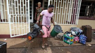Un Nigérian rassemble ses affaires après l'incendie de sa maison par des manifestants xénophobes à Pretoria, le 18 février 2017.