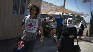 Un humanitaire du CICR aide des pèlerins druzes à traverser les hauteurs du Golan occupées par Israël vers la Syrie, le 15 septembre 2011.