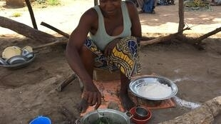 Marceline Huila, a CAR refugee living in Diba 2 refugee site near Baibokoum, Chad, makes the only meal of the day for her family-- boiled sorrel