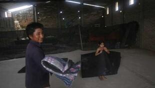 Un trabajador rural lleva una frazada mientras un niño descansa sobre un colchón en un refugio en Tomatlán, al sur del Puerto Vallarta, el 11 de octubre.
