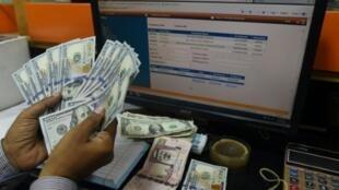 A Pakistani dealer counts US dollars at a currency exchange shop in Karachi on November 30, 2018