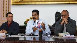 O presidente da Venezuela, Nicolás Maduro, mostra a foto de Hugo Chávez durante coletiva no Palácio Miraflores, em Caracas, em 9 de setembro de 2013.