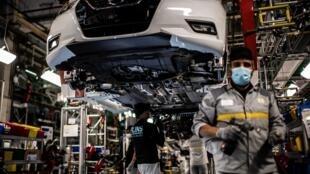 Empleados con mascarilla trabajan en la línea de montaje que produce tanto el vehículo eléctrico Renault Zoe como el vehículo híbrido Nissan Micra, en Flins-sur-Seine, la mayor planta de producción de Renault en Francia, el 6 de mayo de 2020