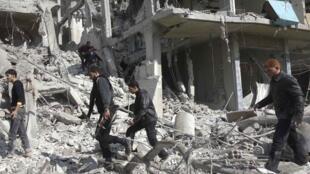 Des résidents et membres de l'Armée syrienne liblre dans les décombres d'un immeuble après le raid aérien de l'armée syrienne. Erbeen, le 27 octobre 2012.
