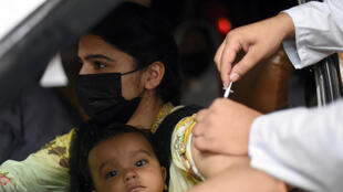 A woman cradling her baby gets a Sinopharm shot at a drive-through vaccination centre in Lahore