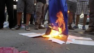 Les manifestants brûlent un drapeau européen devant le Parlement après le vote sur le plan de sauvetage. Nicosie, le 30 avril 2013.