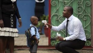 A Lagos, un responsable d'école prend la température d'un enfant avant son entrée en classe.