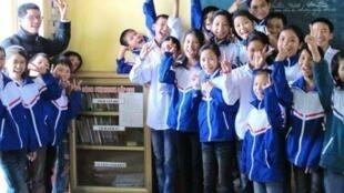 Ông Nguyễn Quang Thạch (góc trên bên trái) trong một lần đưa sách đến với học sinh nông thôn. Ảnh chụp tại trường phổ thông An Lạc, huyện Nam Trực, tỉnh Nam Định.