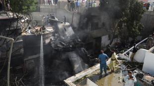 Los bomberos rocían con agua parte del fuselaje del avión de la compañía Pakistan International Airlines que se estrelló en la ciudad de Karachi, el 22 de mayo de 2020 al sur de Pakistán
