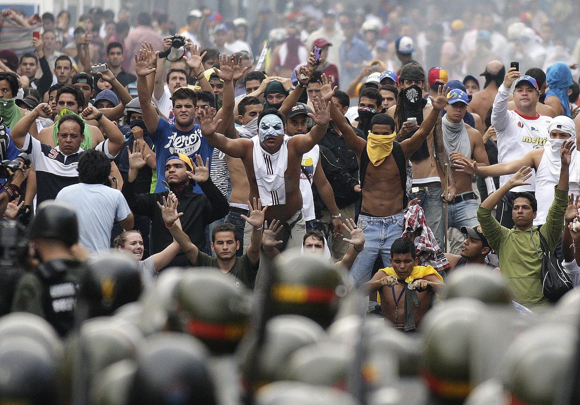 Supporters of opposition leader Henrique Capriles face off against riot police as they demonstrated for a recount of the votes in Sunday's election, in Caracas