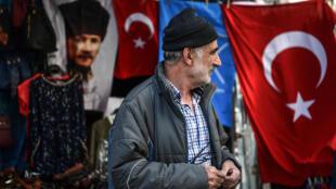 បុរសជនជាតិតួកគិ ឈរក្បែទង់ជាតិតួកគិ និងរូបថត Mustafa Kemal Ataturk បិតាបង្រួបបង្រួមជាតិតួកគិ។ អ៊ីស្តង់ប៊ូល ថ្ងៃទី១៩ ខែមេសា ២០១៨