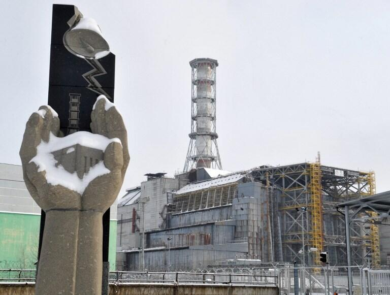 A memorial to victims and the original sarcophagus covering the destroyed Chernobyl reactor.