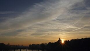 Clouds fill the sky as the sun rises on the River Seine in the early morning light in Paris, 12 December 2013.