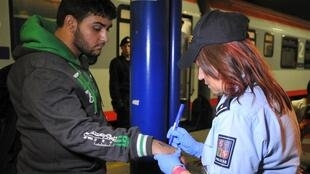 A Czech police officer writes a number on the skin of a refugee in the Czech Republic.