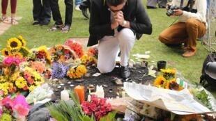 Homem reza pela memória de Nelson Mandela em frente à casa do líder morto em Johanesburgo.