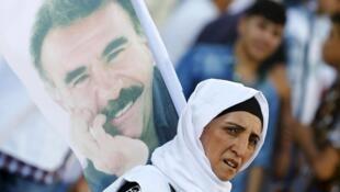 存档图片:Une manifestante kurde arbore un portrait d'Abdullah Öcalan, leader historique du PKK emprionné en Turquie, lors d'une marche solidaire organisée le 1er août à Diyarbakir.