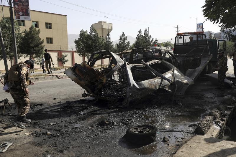 Afghan security personnel inspect the site of a bomb explosion in Kabul, Afghanistan, Saturday, June 12, 2021. Separate bombs hit two minivans in a mostly Shiite neighborhood in the Afghan capital Saturday, killing several people and wounding others, the Interior Ministry said. (AP Photo/Rahmat Gul)