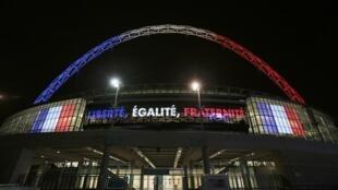"""O arco do estádio Wembley, em Londres, está iluminado com as cores da bandeira da França, e o lema da França """"Liberdade, Igualdade, Fraternitdade"""" está estampado no local. 16 de novembro de 2015."""