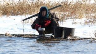 Một phụ nữ Bắc Triều Tiên đang lấy nước bên sông Áp Lục (Yalu), gần hạt Sakchu (Ảnh chụp từ phía Trung Quốc, ngày 17/12/2014).