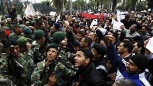 Quân đội cố ngăn chận đoàn người biểu tình trước trụ sở đảng Tập hợp Hiến pháp Dân chủ của cựu Tổng thống Ben Ali ngày 20/1/11, đòi các bộ trưởng là người của đảng này phải rời chính phủ.