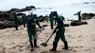 Des employés municipaux nettoient la plage de Itapua, à Salvador da Bahia, polluée par la marée noire (image d'illustration).