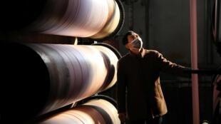 Một công nhân đeo khẩu trang phòng hộ tại một xưởng dệt may ở Hàng Châu (Hangzhou), tỉnh Chiết Giang (Zhejiang), Trung Quốc. Ảnh chụp ngày 20/02/2020