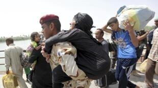 Un militaire irakien aide une habitante à fuir les combats près de Ramadi, le 24 mai 2015.