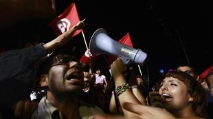 Protesto noturno diante da sede da Assembleia Nacional Constituinte na Tunísia.