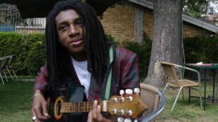 Rap star Namesix posing with a traditional Kabosy guitar